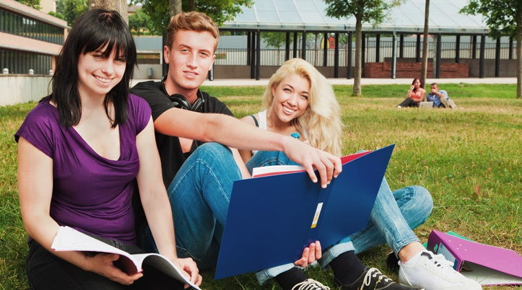 students sitting in the grass, learning